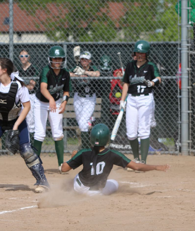 Maloney's Elizabeth Barton, left and Taylor Trowbridge, right, look on as Tauryn Askew, center, slides into home plate. May 22nd, 2019 | Spencer Davis, Record Journal