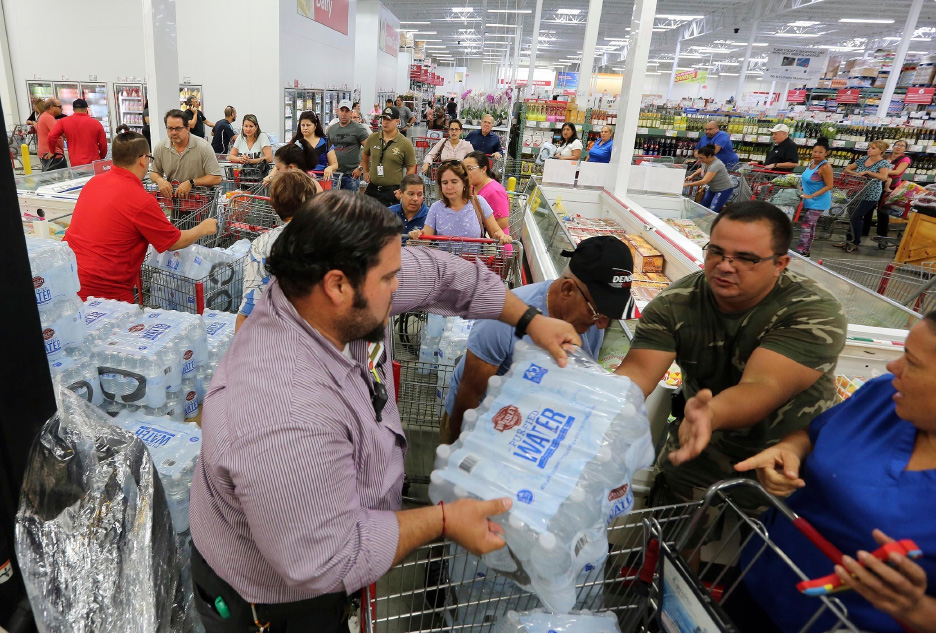 FILE- This Sept. 5, 2017 file photo shows residents in a long line waiting to purchase water at BJ Wholesale in preparation for Hurricane Irma in Miami. With images of Hurricane Harvey