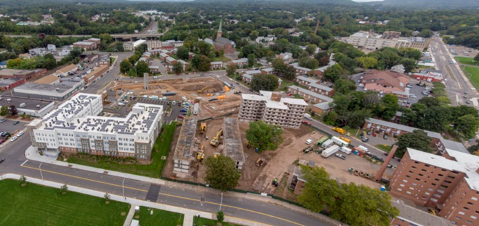 Demolition of the Mills Memorial Apartments continues Sept. 24, 2018 on the right as construction of the Meriden Commons II takes place in the background. | Richie Rathsack, Record-Journal
