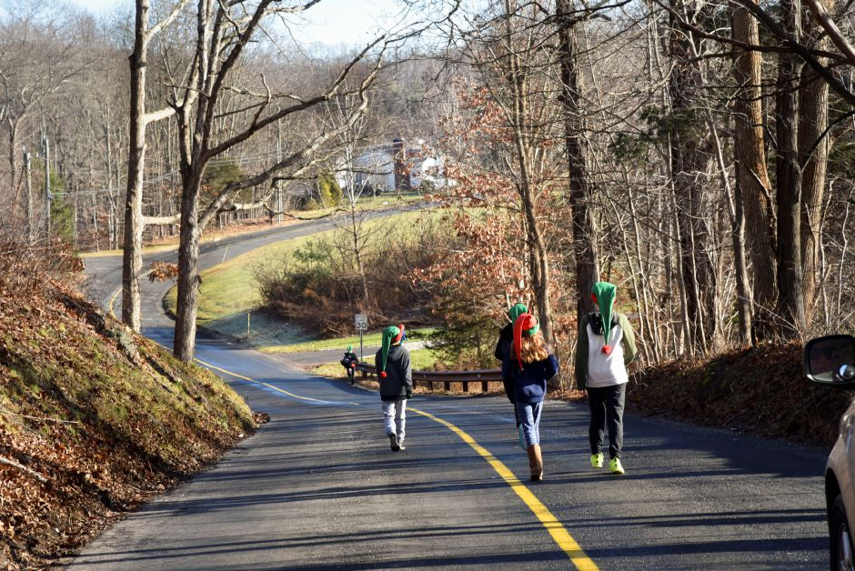 A group of students, with parents trailing in a nearby car, run along Haddam Quarter Road in Durham wearing elf hats while collecting donations door-to-door during the 13th annual Community Round-up in Durham and Middlefield on Saturday, Dec. 1, 2018. The event collected more than 13,000 food items and about $3,500 to go to Durham and Middlefield Social Services, and Amazing Grace in Middletown. | Bailey Wright, Record-Journal