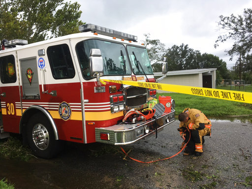 A member of the Orange County fire department plays with a puppy rescued from a flooded neighborhood in Orange County, Fla., Monday, Sept. 11, 2017. The National Guard and local firefighters evacuated homes by boat as Hurricane Irma bore down on the county overnight. Rescuers said residents left the puppy in a cage, and it was almost drowning when firefighters found it. (AP Photo/Claire Galofaro)