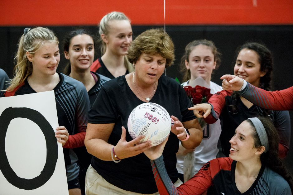 Cheshire's head coach Sue Bavone admires the volleyball signed by her team celebrating her 500th win Tuesday at Cheshire High School in Cheshire October 9, 2018 | Justin Weekes / Special to the Record-Journal