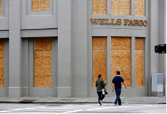 A couple walks by a boarded up Wells Fargo bank in downtown Charleston, S.C., Sunday, Sept. 10, 2017 as tropical storm force winds are suppose to hit the area Monday. (AP Photo/Mic Smith)