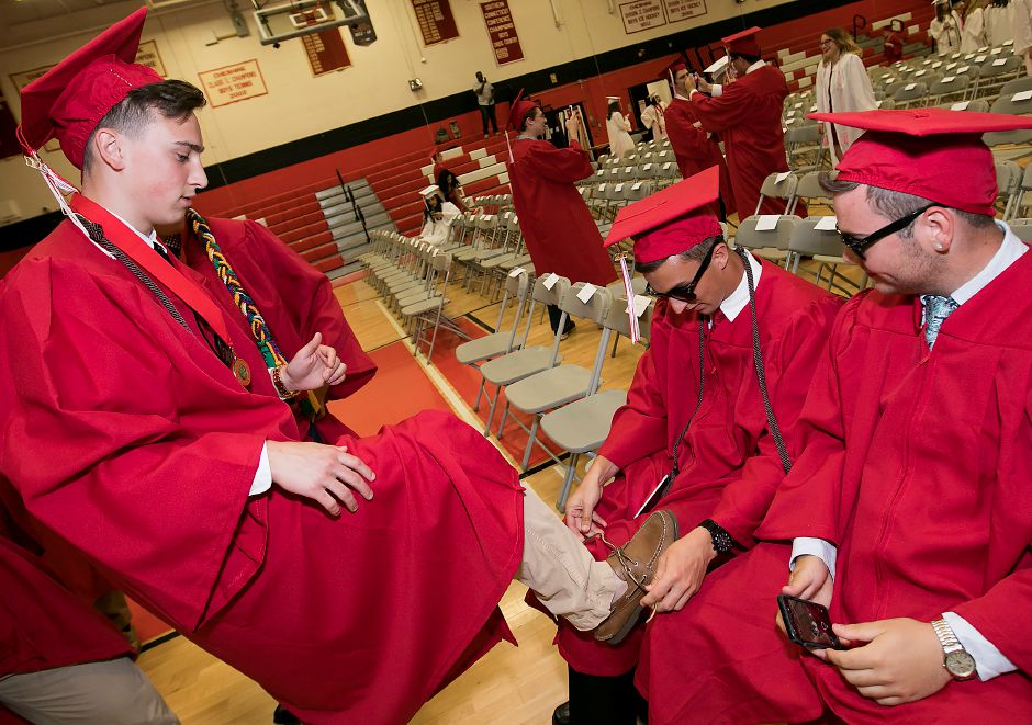 Graduate Evan Russo, left, gets help with his shoelace from friend, Andre Pereira, next to Braden Mach, right, before the start of graduation ceremonies at Cheshire High School, Wednesday, June 14, 2017. | Dave Zajac, Record-Journal