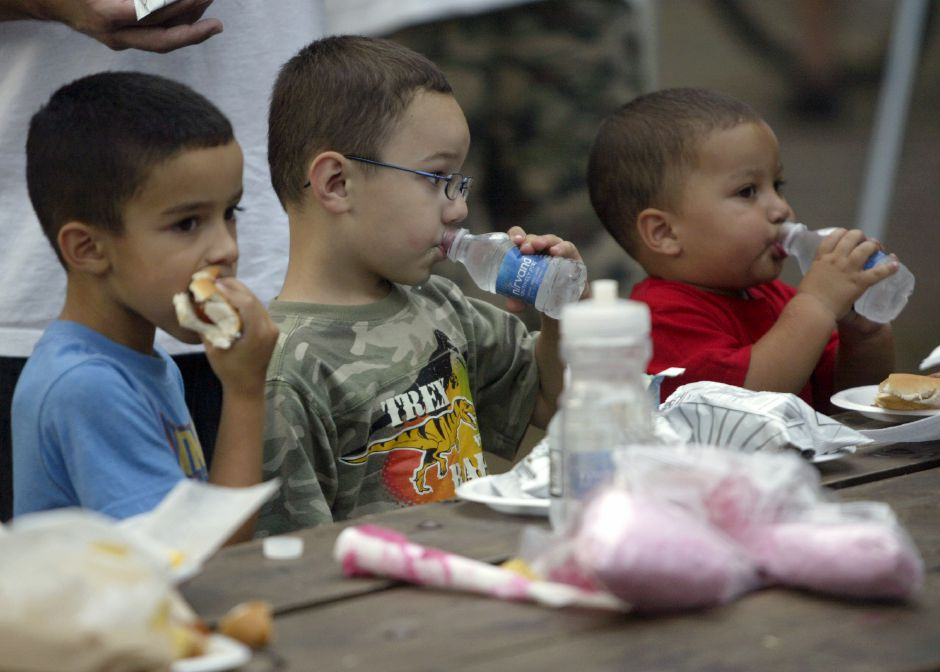 From left, Joshua Rosario, 6, Jordan Marks, 6, and Daniel Garcia, 19 months, enjoy the free food and drinks provided by the Lions Club at the annual National Night Out on Tuesday, August 3, 2010 from City Park in Meriden. (Rob Beecher / Record-Journal)
