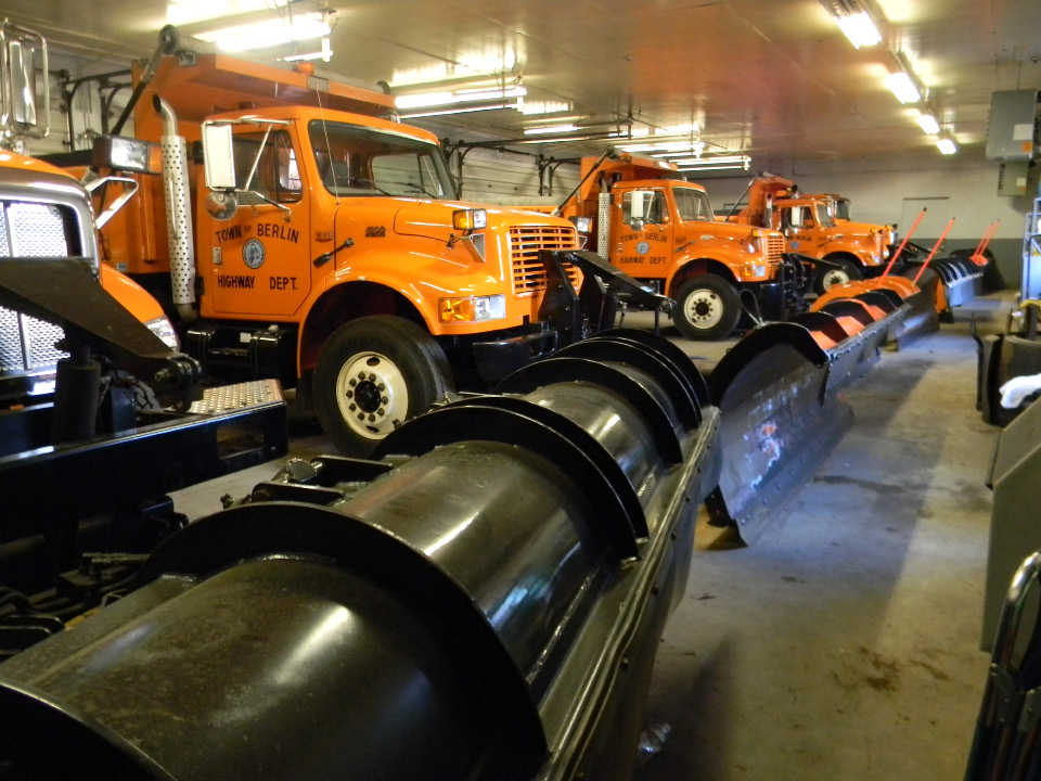 Town trucks parked in a line with the plows waiting to be installed.| (Daniel Jackson / The Berlin Citizen)