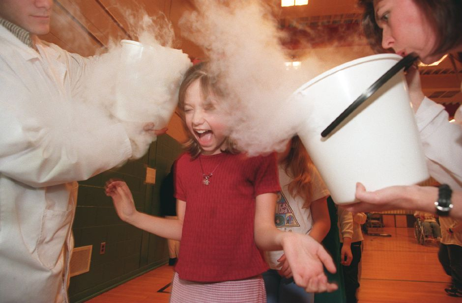 RJ file photo - Katherine Perkins, a third-grader, experiences carbon dioxide fog from dry ice during a science schow at Rock Hill School in Wallingford, Dec. 1998. Tony Allen, left, and Terry Wright, both of a company called Mad Science, put on the demonstration.