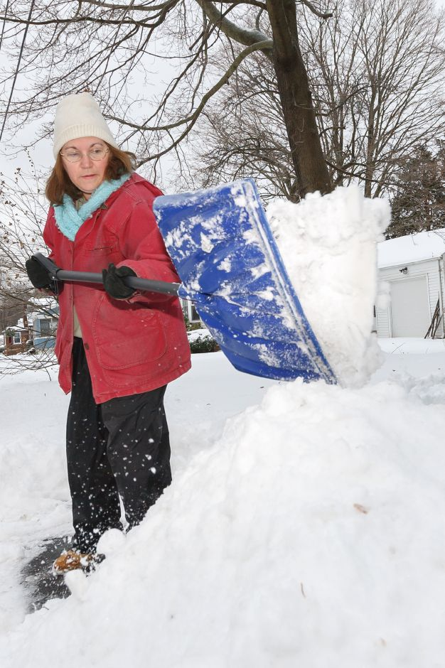 Anna Gunther of Wallingford shovels snow at the end of her driveway Sunday after a winter storm left several inches December,15 2013 | Justin Weekes / For the Record-Journal