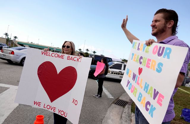 A small group of parents and neighbors welcome returning faculty and administration at Marjory Stoneman Douglas High School in Parkland Fla., Monday, Feb. 26, 2018. Today marked the first day back for teachers at the school.  (Joe Cavaretta /South Florida Sun-Sentinel via AP)