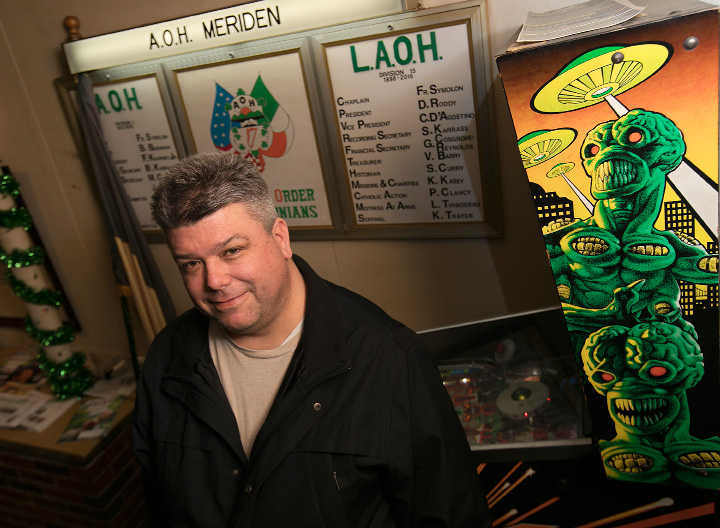 "Brian Brennan, of Wallingford, stands next to his ""Attack From Mars"" pinball machine at the Meriden A.O.H. club on Friday. Brennan is grand marshal for this year's annual St. Patrick's Day parade in Meriden.