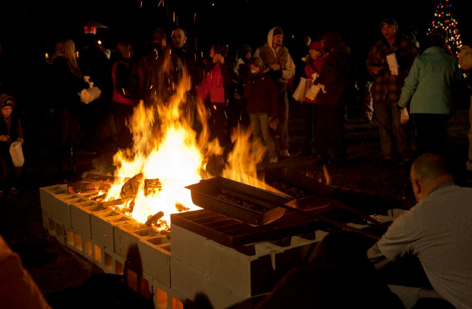 Attendees of the Christmas in the Village celebration gather around the fire while chestnuts are roasted in front of Faith Living Church in downtown Plantsville Thursday night, Dec. 6, 2012. (Christopher Zajac / Record-Journal)