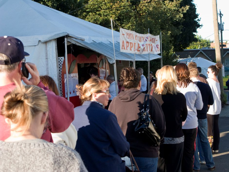 FILE PHOTO – About 45 people wait in line for hot apple fritters from the Zion Lutheran Church Apple Fritter Booth at the Apple Harvest Festival on Oct. 8, 2010. The fritter booth is located on a public parking lot which the town leases from First Congregational Church. | Christopher Zajac, Record-Journal.