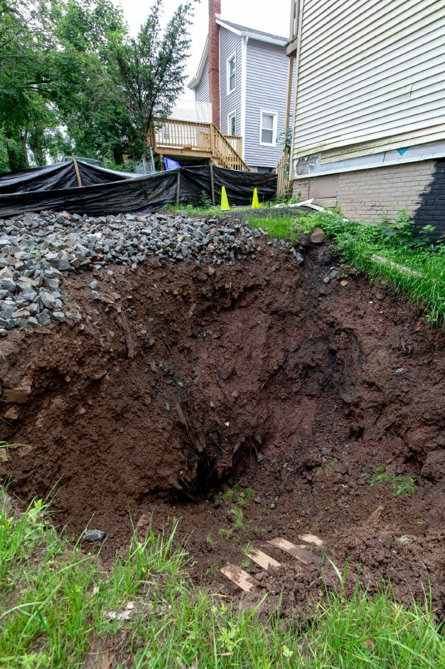 A sinkhole has opened in the backyard of a home at 170 Liberty Street in Meriden. The hole, which a property manager estimates is 16 feet deep, has reopened despite two attemps by the city to fill it with soil and gravel since it first appeared Easter morning. | Devin Leith-Yessian/Record-Journal