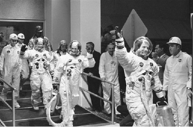Apollo 11 astronauts Commander Neil A. Armstrong, Michael Collins and Edwin E. Aldrin Jr. wave in Cape Kennedy, Florida on July 17, 1969 as they walk from the Manned Spacecraft Operations Building their transfer van which takes them to the moon spacecraft. (AP Photo/Bill Smith)