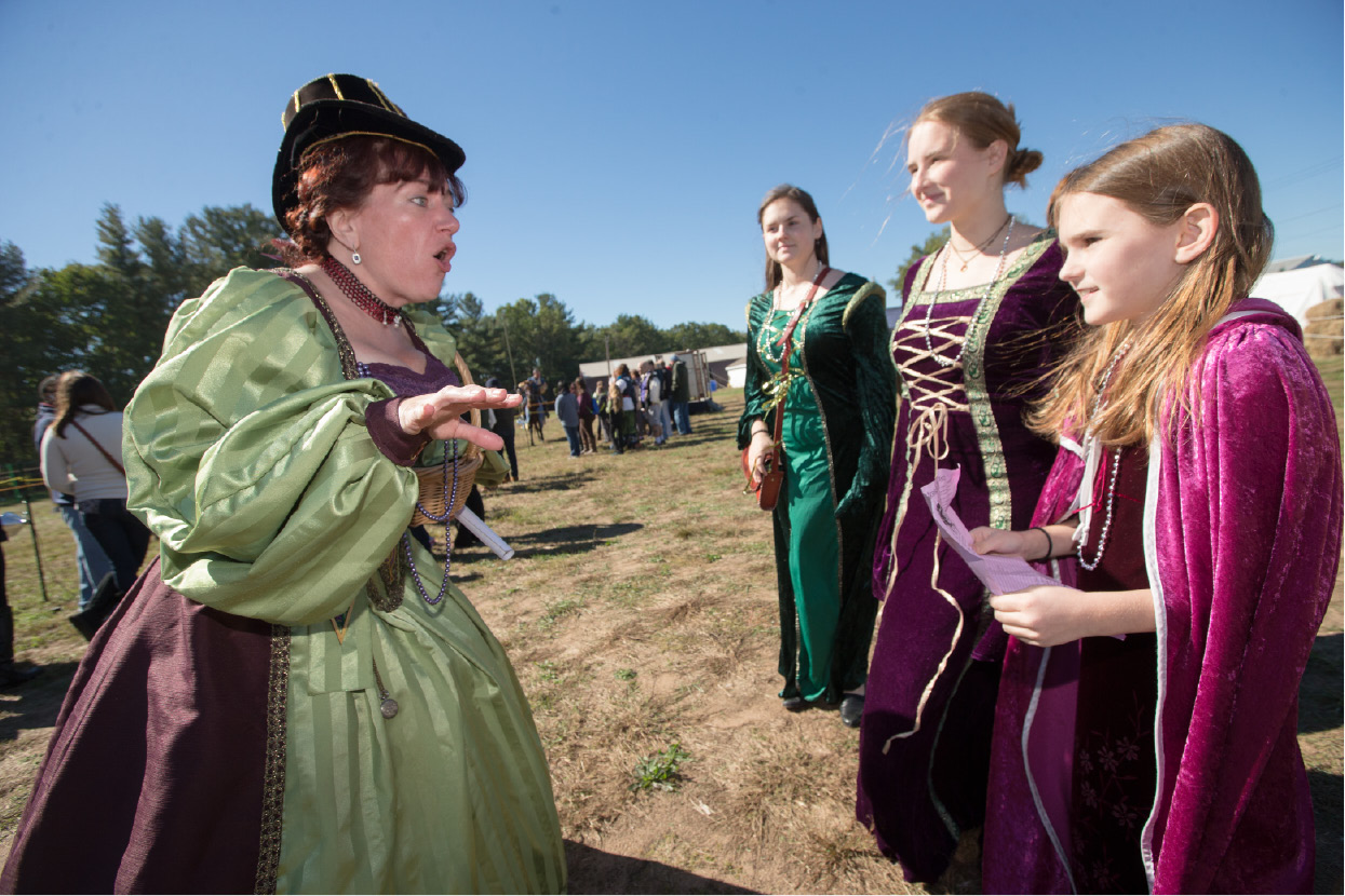 Jenna Bullock-Papcin of Mystic plays Lady Mandrake gives a clue to her mystery to Lydia Barnes 9 right Hope Barnes 17, and Anna Barnes 15 of North Haven Monday during the Connecticut Renaissance Faire at the North Haven Fair Grounds. | Justin Weekes / Special to The Sun