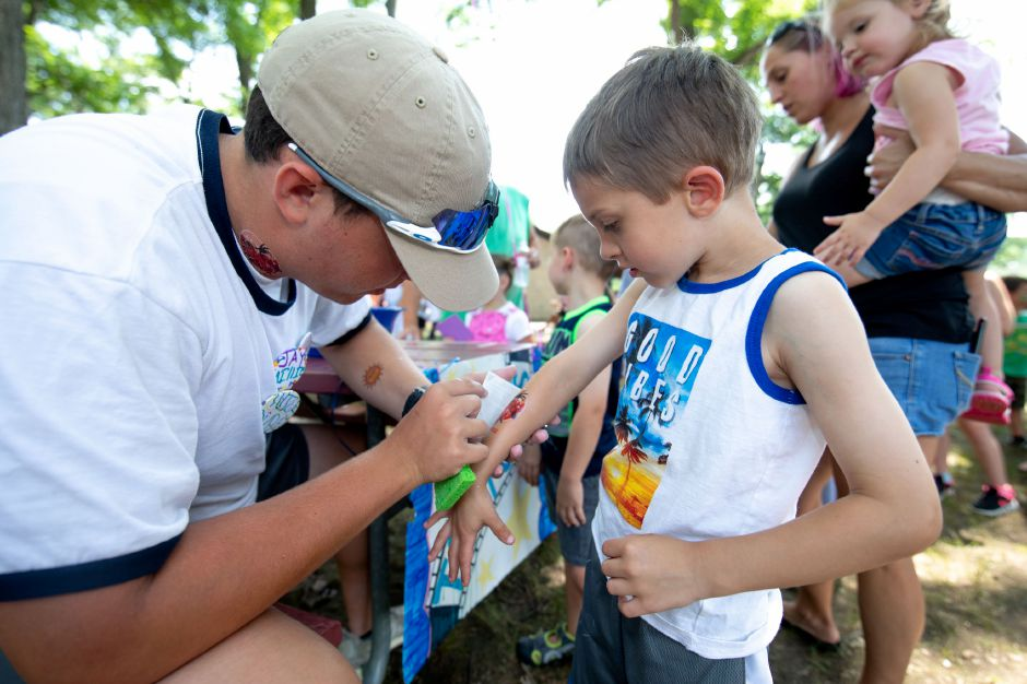 Parker Snyder, 6, gets a temporary tattoo from Alec Karal at Plainville