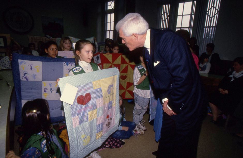 RJ file photo - Meriden Mayor Joseph J. Marinan Jr. tals with Larissa Erazmus of the Roger Sheman School Girl Scouts March 10, 1994. The mayor accepted 17 quilts sewn by local Girl Scouts for babies with AIDS.