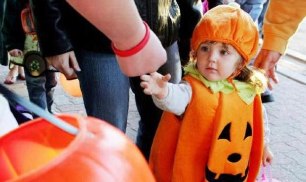 A trick-or-treater puts her hand out for candy. | Associated Press