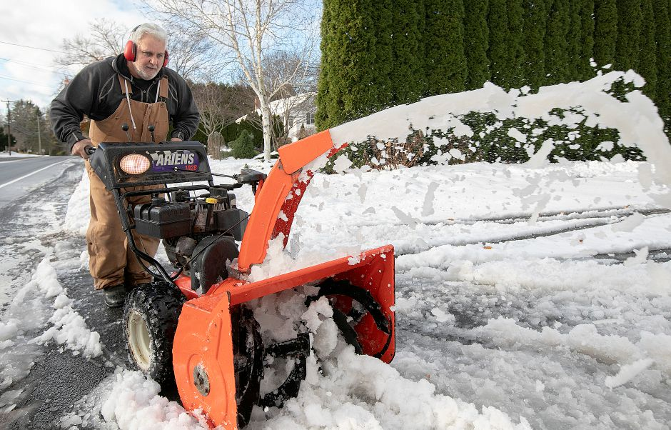 Rick Deschaine, of Southington, clears snow and slush from a neighbor's driveway on Meriden Avenue, Fri. Nov. 16, 2018. Dave Zajac, Record-Journal