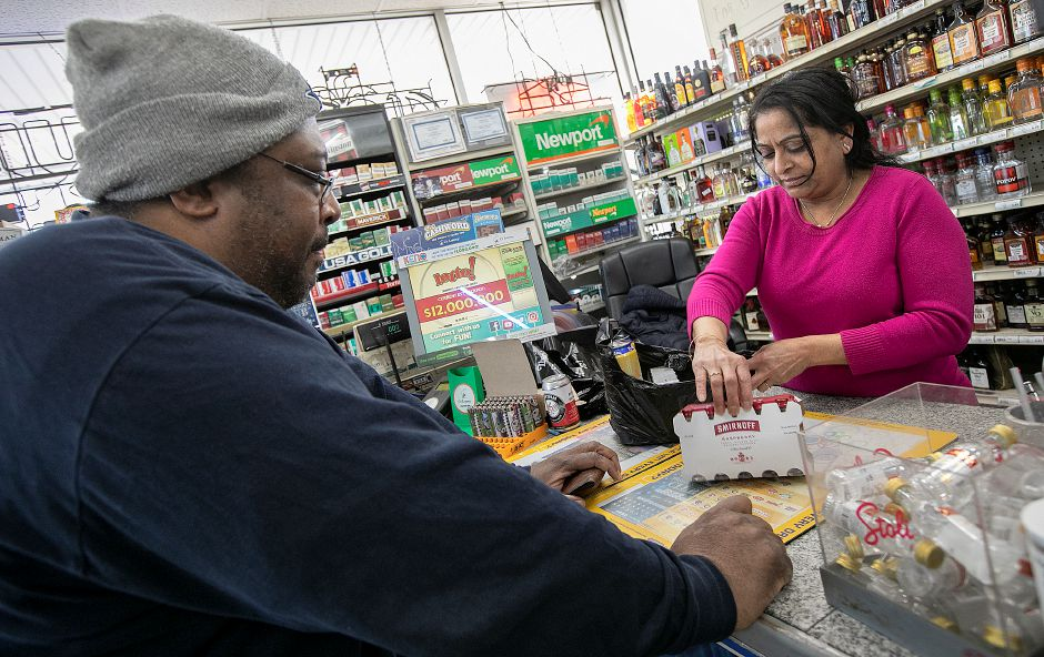 "Champak Patel talks at his Grog Shop of Meriden liquor store on Old Colony Road in Meriden, Thurs., Feb. 21, 2019. Gov. Ned Lamont is proposing a 25 cent deposit on wine and glass liquor bottles and a five cent deposit on miniature ""nip"" bottles in his biennial budget released this week. Dave Zajac, Record-Journal"