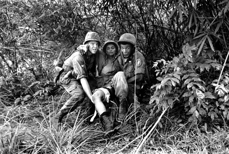 Trying to avoid intense sniper fire, two American medics carry a wounded paratrooper to an evacuation helicopter during the Vietnam War on June 24, 1965. A company of paratroopers dropped directly into a Viet Cong staging area in the jungle near Thoung Lang, Vietnam. The medics are Gerald Levy, left, from Meriden; and PFC Andre G. Brown, of Chicago. The wounded soldier is not identified. Horst Faas, Associated Press