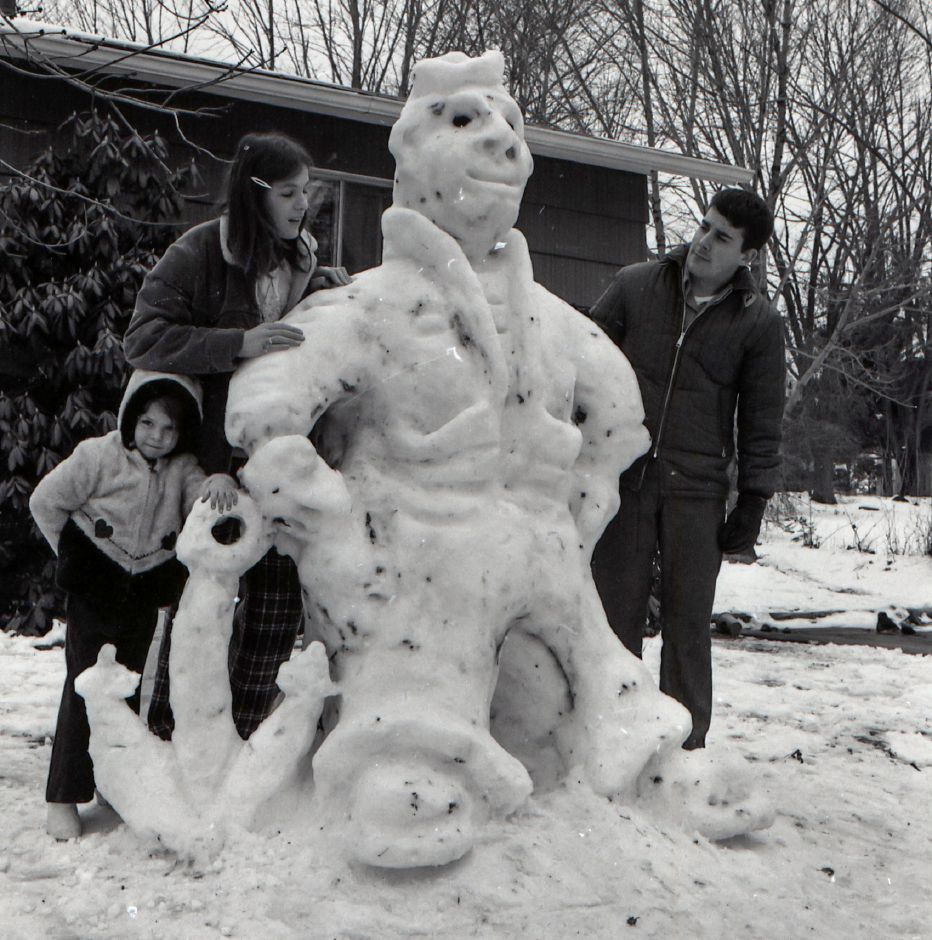 A family stands next to a snow scuplture at their home on Gardner Street in Meriden, February 1975.