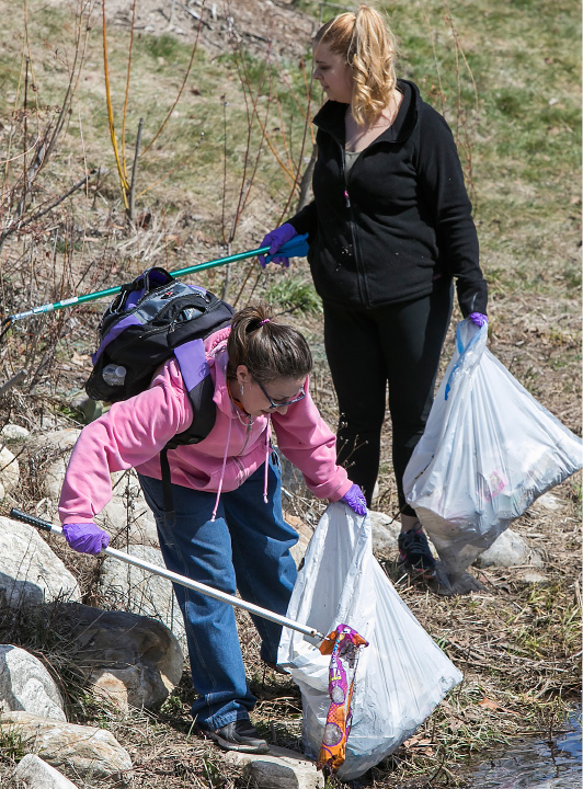 Sharon Milano, bottom, and friend Elizabeth Frederick, both of Meriden, help clean litter from the banks of Harbor Brook on the Meriden Green on Wednesday.| Dave Zajac, Record-Journal
