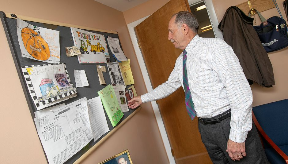 Henry McCully, director, looks over clippings and mementos in his office at Wallingford Public Works on Town Farm Road, Wed., Mar. 13, 2019. McCully is retiring after more than 35 years with the department. Dave Zajac, Record-Journal