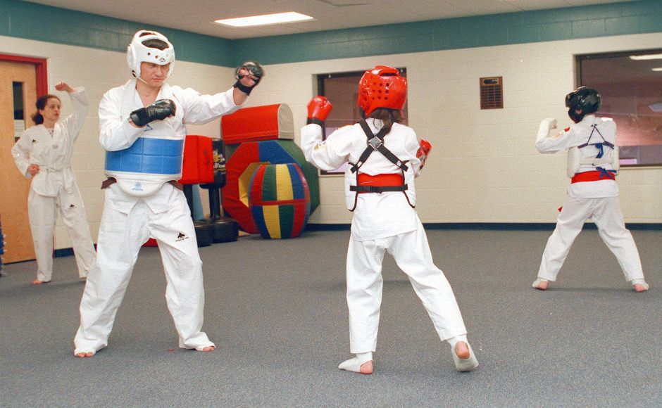 RJ file photo - Ildong Kim, left, of Milford, spars with his daughter, Ina Kim, 11, during a Taw Kwon Do demonstration at the Meriden Y Jan. 10, 1999.