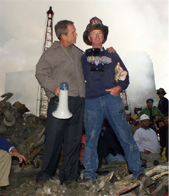 **ADVANCE FOR SUNDAY, JAN. 4 AND THEREAFTER -- FILE ** In this Sept. 14, 2001 file photo, as rescue efforts continue in the rubble of the World Trade Center, President George W. Bush puts his arms around firefighter Bob Beckwith while standing in front of the World Trade Center in New York. (AP Photo/Doug Mills, File)