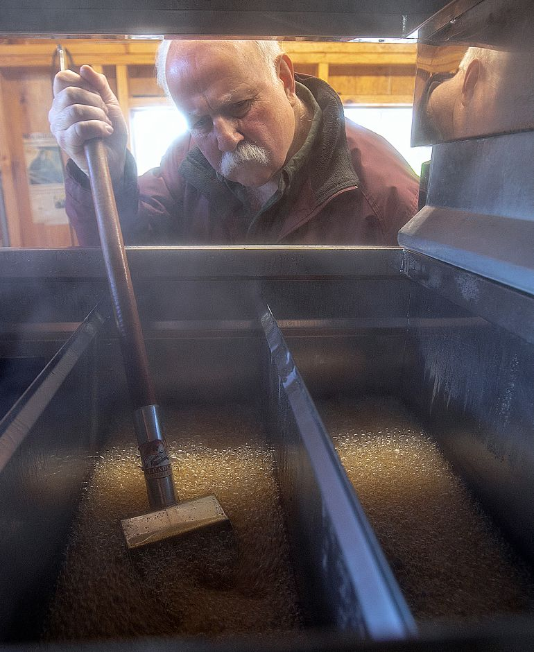 Michael Karabin of Karabin Farms uses a small shovel to keep the fluid moving in an evaporator while making maple syrup at the Southington farm at 894 Andrews St., Tues., Mar. 19, 2019. Dave Zajac, Record-Journal