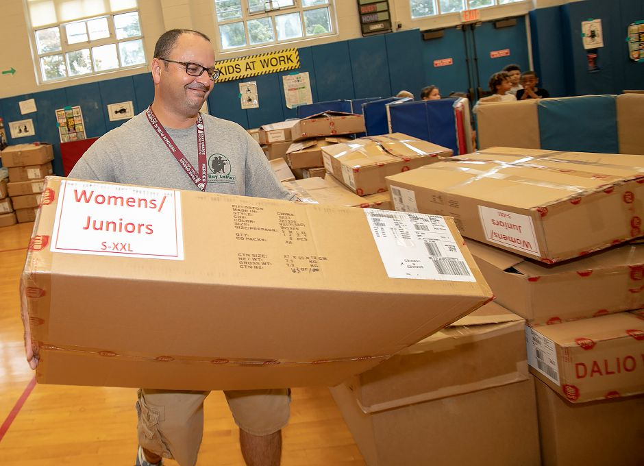 David Cardona stacks a box of coats during the annual coat donation by the Dalio Foundation at Hanover School in Meriden Thursday. Over 1,000 children in Meriden's public school system received new coats on Thursday to prepare for the winter months.