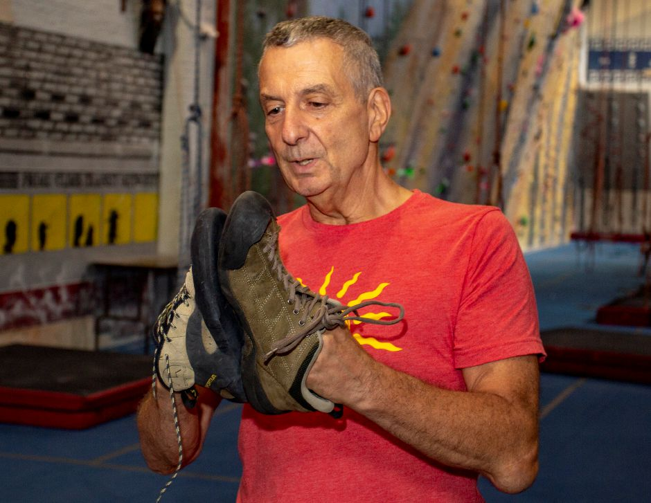 Brien Roscetti, owner of Prime Climb indoor rock climbing in Wallingford, shows off the difference bewteen regular street shoes and rock climbing shoes Aug. 20, 2018. | Richie Rathsack, Record-Journal