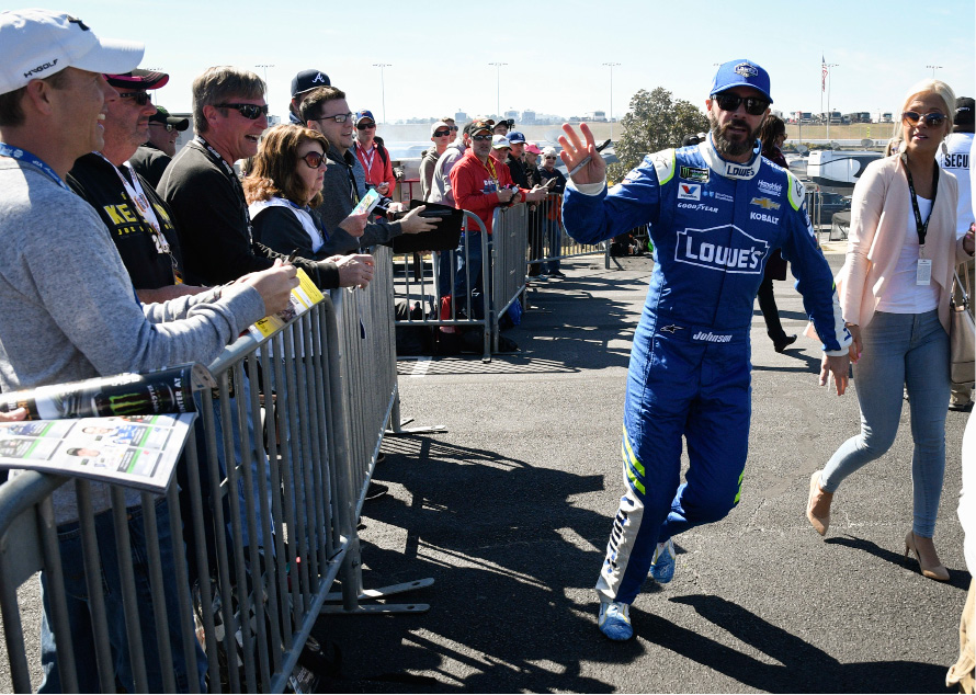 Driver Jimmie Johnson waves to fans as he passes them on the way to the garage to practice for the NASCAR Monster Cup series auto race at Atlanta Motor Speedway in Hampton, Ga., Saturday, March 4, 2017. (AP Photo/John Amis)