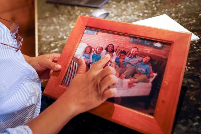 Margery Koveleski shows a picture of her family when they moved from New York City to Ohio, during an interview in the showroom of their store Design Sleep in Yellow Springs, Ohio on Thursday, Aug. 23, 2018. It was initially a challenge for the Koveleskis' children to be the new, mixed-race kids in an area less diverse than Queens. And Michael struggled to find work in the shaky post-9/11 economy. (AP Photo/John Minchillo)