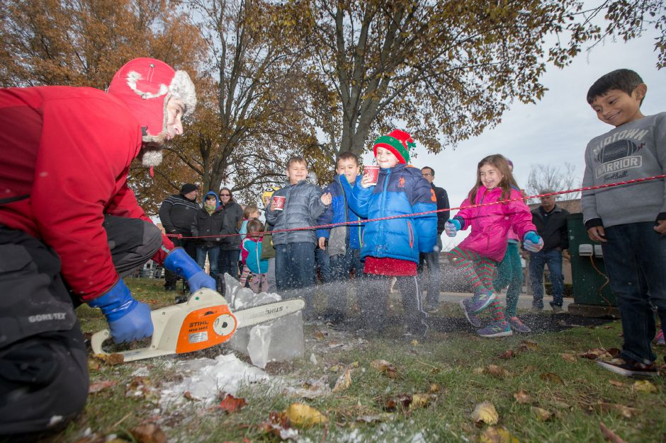 Ice carver Gary Costa of Cheshire sprays kids with slush from his chain saw Saturday during Season of Celebration at the Town Hall in Wallingford December 2, 2017 | Justin Weekes / For the Record-Journal