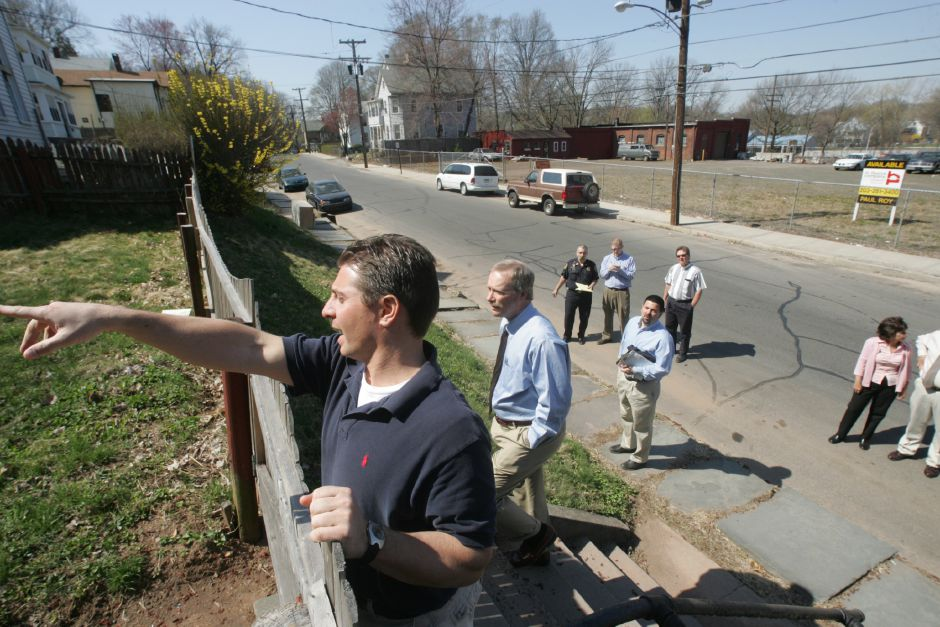 Meriden Mayor Mark Benigni, left, points to something while speaking with Acting City Manager Lawrence J. Kendzior, right, as they look over a a fence during a code enforcement walk in Meriden Tuesday afternoon April 19, 2005. The code enforcement walk was with city officials on several downtown streets. Chris Angileri/Record-Journal.