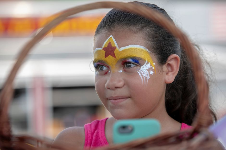 Miah Velazquez, 9, of New Britain, wears a Wonder Woman face while helping grandmother Tina Rodriguez, a Hartford HealthCare Outreach Educator, during the Community Health Center's health fair on the Meriden Green, Thursday, August 16, 2018. Community Health Center, Inc. is celebrating National Health Center week with a series of fairs around the state, including Meriden's event. Dave Zajac, Record-Journal