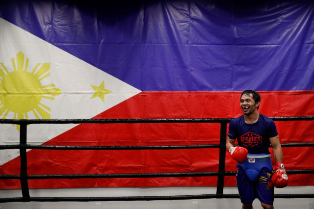 Standing in front of a large Filipino flag, boxer Manny Pacquiao smiles while training at the Wild Card Boxing Club Monday, Jan. 14, 2019, in Los Angeles. The Filipino legend is in the winter of his career, gearing up for what could be one big last fight. Saturday