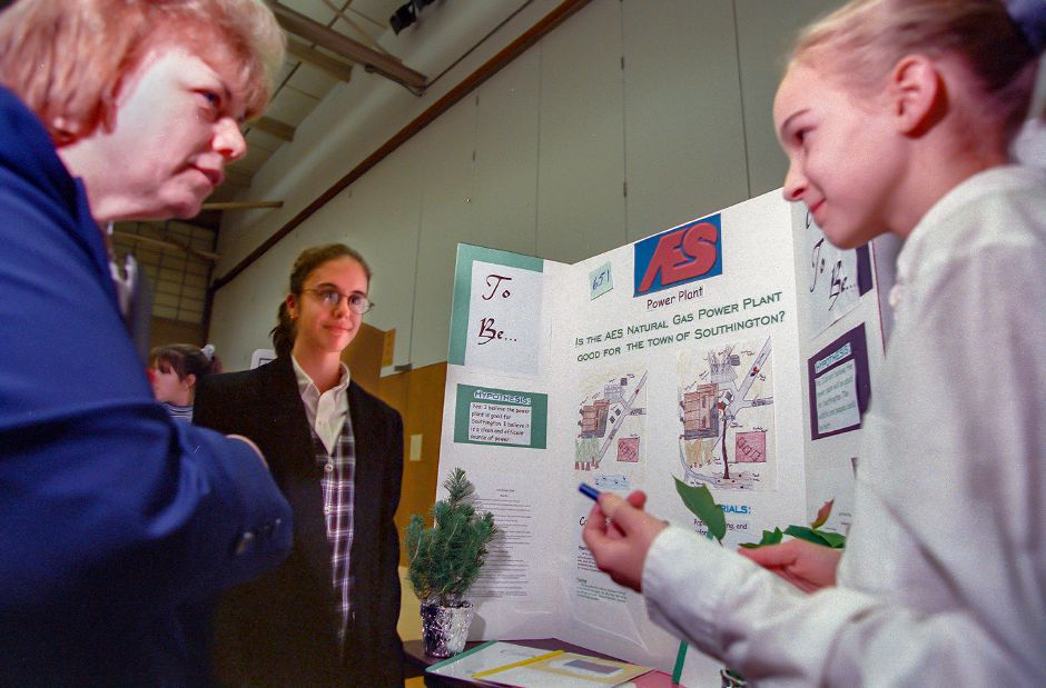RJ file photo - Studens Nina DePalma, center, and Marisa Soboleski, right, discuss their project about the proposed AES Power Plant with science fair judge Dale Riedinger during the fair at John F. Kennedy Middle School in Southington Jan. 1999.