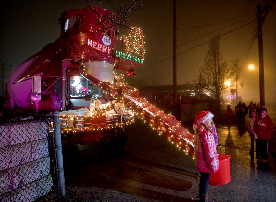 "Makayla Carlson, 10, of Southington poses for a picture next to a decorated cement truck parked at F & F Concrete during ""Christmas in the Village"" in Plantsville, Thursday, December 5, 2013. 