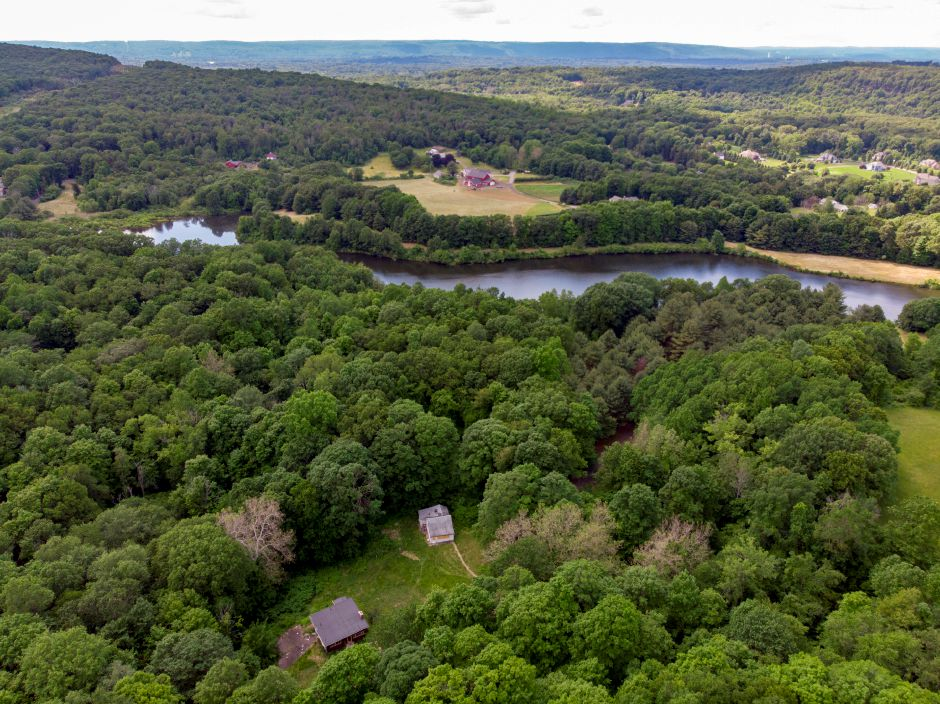 The city of Meriden is considering purchasing the two homes in the foreground, which have septic tanks that leak into nearby Kenmere Reservoir. The homes are vacant, shuttered and owned by a bank, June 6, 2019. | Richie Rathsack, Record-Journal