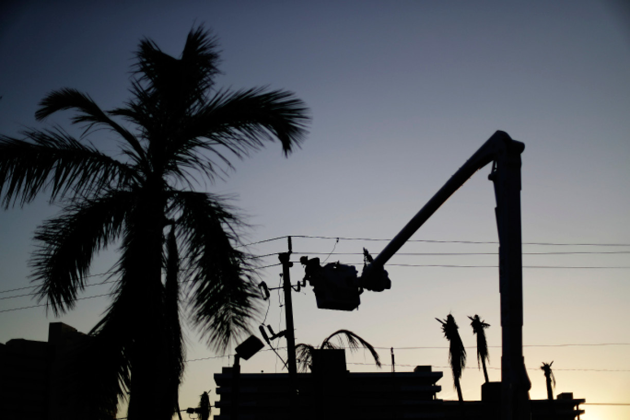 A worker is silhouetted against the setting sun as he works on a power line in the aftermath of Hurricane Irma in Marco Island, Fla., Tuesday, Sept. 12, 2017. Florida officials say crews are restoring power across the state, but 9.5 million people remain without electricity. State Emergency Management Center officials say they restored power to 1.7 million homes and businesses on Tuesday. (AP Photo/David Goldman)