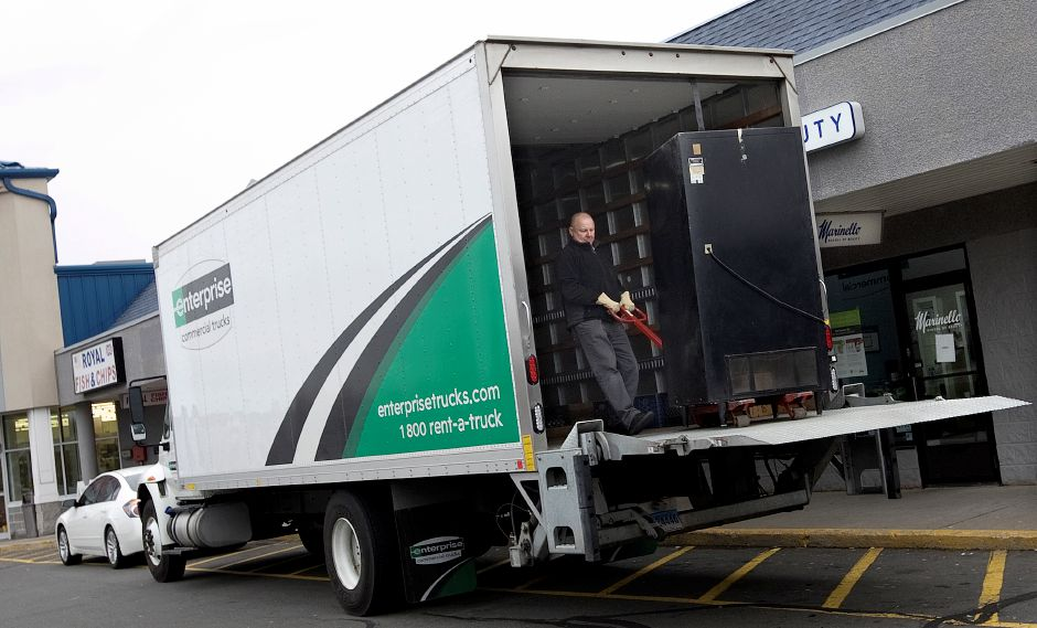 A man loads a vending machine from Marinello School of Beauty into a truck at the 1321 E. Main St. school in Meriden, Thursday, February 4, 2016. Marinello School of Beauty closed its east side campus Thursday. | Dave Zajac / Record-Journal