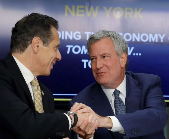 FILE - In this Nov. 13, 2018 file photo, New York Gov. Andrew Cuomo, left, and New York City Mayor Bill de Blasio shake hands during a news conference in New York. Cuomo and de Blasio trumpeted Amazon