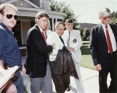 Former PTL leader Jim Bakker (center) is escorted to a car by U.S. Marshals from his attorney