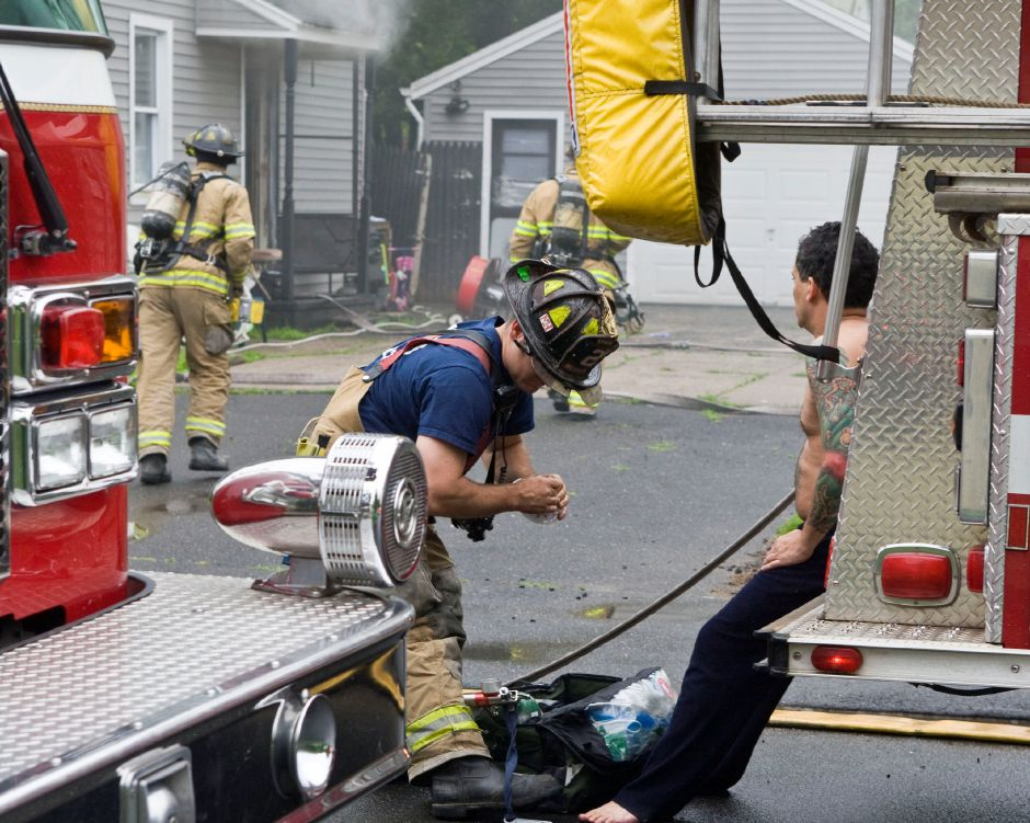 A fire fighter sets up an oxygen mask for a man, right, who escaped the house at 255 Douglas Drive after a small fire broke out in the residence in South Meriden, Friday morning, June 12, 2009. The man tried to extinguish the fire with a garden hose. The man was transported by Hunter