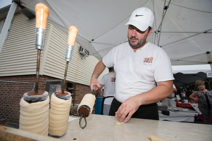 Radu Sirbv of Twister Cakes NY wraps dough around a drum before baking them to make Twister Cakes, a carmel coated with to order toppings Sunday during the Hungarian Festival at the Hungarian Community Club in Wallingford Sep. 18, 2016 | Justin Weekes / For the Record-Journal