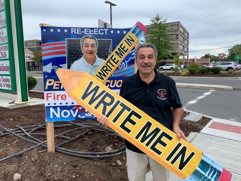 Peter Criscuolo poses near his campaign sign at Washington Commons Plaza holding a sign urging voters to mark him as a write in candidate this upcoming election. Photo by Everett Bishop, North Haven Citizen.