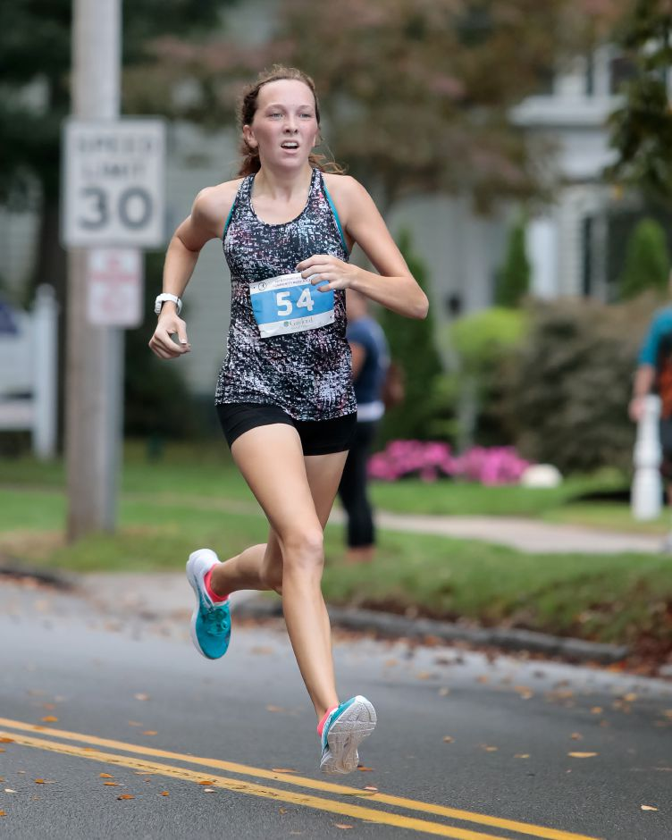 Hometown girl Liz Fengler was the first female and second runner overall across the 5K finish line in Sunday's Fishbein/YMCA Community Road Race in Wallingford. | Justin Weekes / Special to the Record-Journal